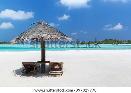 travel, tourism, vacation and summer holidays concept - palapa and sunbeds over sea and sky on maldives beach - stock photo