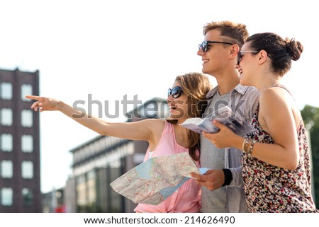 travel, tourism, vacation, summer and people concept - smiling friends with map and city guide pointing finger outdoors - stock photo