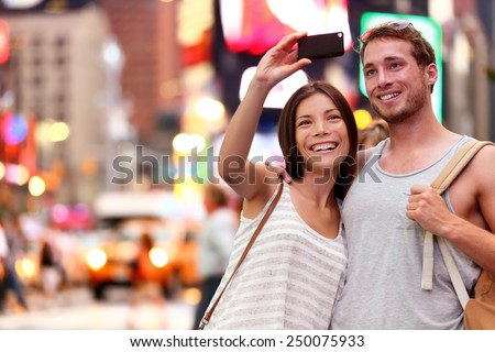 Travel tourist couple taking selfie with smartphone in New York City, USA. Self-portrait photo on Times Square at night. Beautiful young tourists having fun, Manhattan, USA. Asian woman, Caucasian man