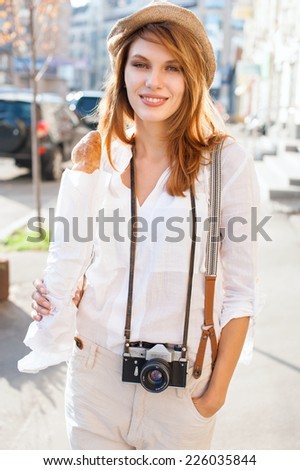 Travel tourist woman with camera and baguette / photography of young Caucasian woman outdoors