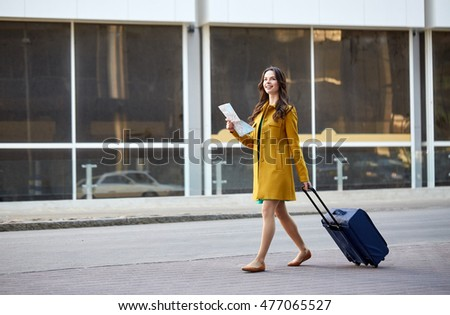 travel, trip, tourism, people and vacation concept - happy young woman with carry-on travel bag and map walking along city street