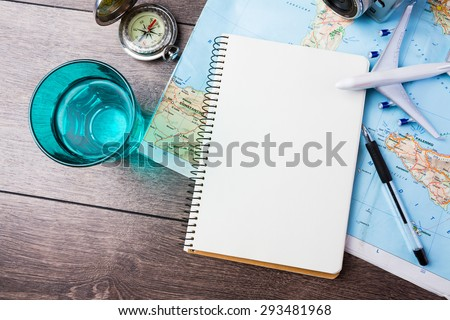 travel , trip vacation, tourism  mockup - close up of compass, glass of water note pad, pen and toy airplane and touristic map on wooden table. Empty space you can place your text or information. - stock photo