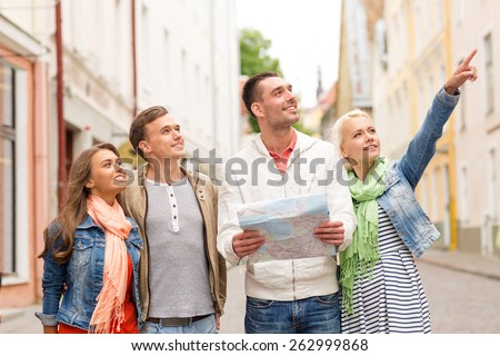 travel, vacation and friendship concept - group of smiling friends with city map exploring city - stock photo