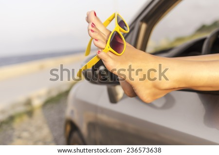 Travel vacation freedom beach concept. Female legs out of car window. Toned photo. - stock photo