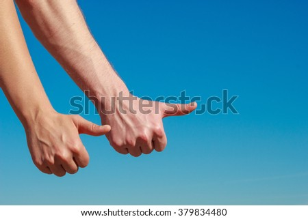 Travel vacation hitchhiking and happiness concept. Male hands thumbing and hitch hiking outdoor, thumb up gesture against blue sky