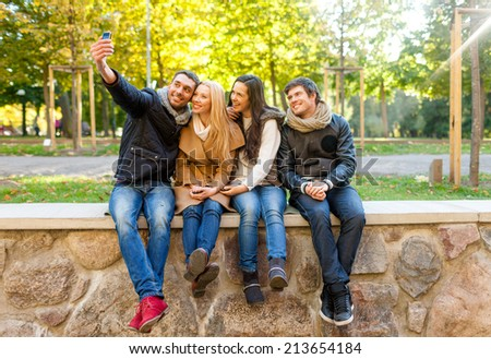 travel, vacation, people, technology and friendship concept - group of smiling friends making self portrait with smartphones in city park - stock photo