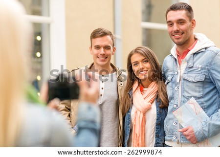 travel, vacation, technology and friendship concept - girl picturing group of friends with map in city