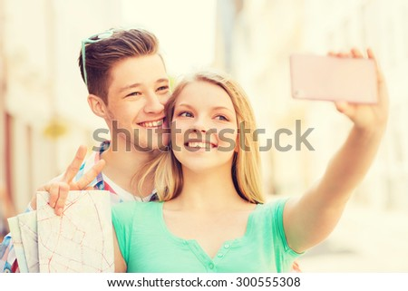 travel, vacation, technology and friendship concept - smiling couple with smartphone in city - stock photo