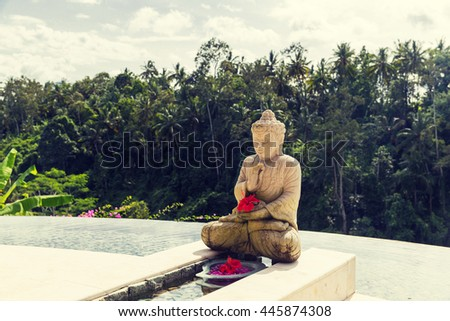 travel, vacation, tourism, religion and luxury concept - beautiful view from infinity edge pool with buddha statue to tropical woods in asia - stock photo
