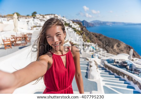 Travel Vacation Tourist Selfie. Woman taking self-portrait photo on Santorini, Greek Islands, Greece, Europe. Girl on summer vacation visiting famous tourist destination having fun smiling in Oia.  - stock photo