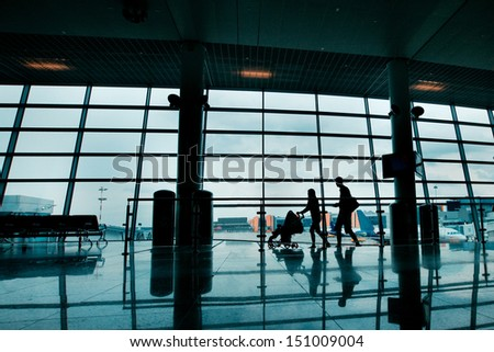 travel with children, silhouettes of family with buggy at the airport - stock photo