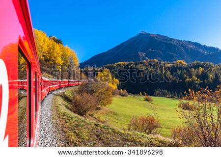 Travel with train of Rhaetian Railway in golden autumn through the line of Glacier Express in Engadin, Canton of Grisons, Switzerland. - stock photo