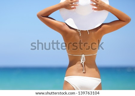 Travel woman on beach enjoying blue sea and sky wearing white beach sun hat and bikini. Beautiful pretty stylish young asian model from behind on vacation holidays. - stock photo