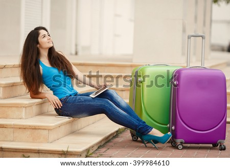 Travel woman with suitcase and laptop gps, tourist girl with vacation bags at bus station, Elegant woman with a suitcase travel at city streets vacation europe,soft grain filter instagram like.   - stock photo