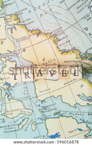 Travel word made from wooden letter blocks on a vintage map. Travel, holiday concept
