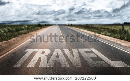 Travel written on rural road - stock photo
