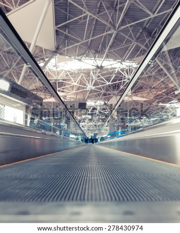 travelator at the airport and a metal roof and blurred lights