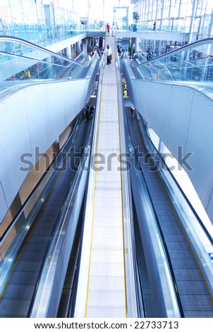 Travelator with people in airport. No recognizable faces or brandnames. Toned Cold.