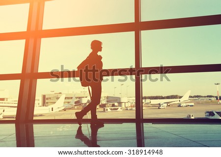 traveler at the airport. silhouette of a girl with a backpack. business and travel - stock photo