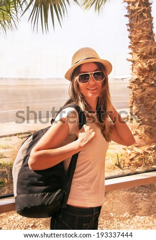 Traveler attractive girl is near the airport window. Passenger woman with backpack is in terminal. Air travel concept with happy female, who standing with hand luggage (Sharm El Sheikh, Egypt).   - stock photo