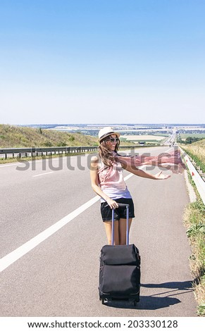 Traveler attractive smiling girl is walking on highway in the summer day. Caucasian woman has suitcase. Happy active young female model. Travel (vacations) and adventure concept. Copy space, outdoor. - stock photo