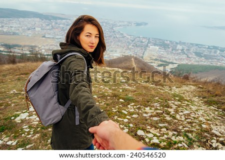 Traveler beautiful young woman holding man's hand and leading him on nature outdoor. Couple in love. Focus on woman. Point of view shot - stock photo