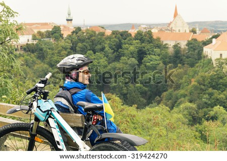 Traveler from Ukraine resting after bike tour, the Ukrainian flag is attached to the bike. - stock photo