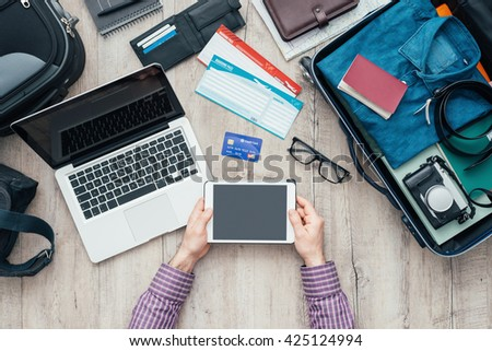 Traveler getting ready for a trip, he is packing his bag and using a digital touch screen tablet, flat lay