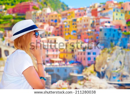 Traveler girl enjoying colorful cityscape, spending summer vacation in Europe, Italy, Cinque Terre, beautiful painted buildings