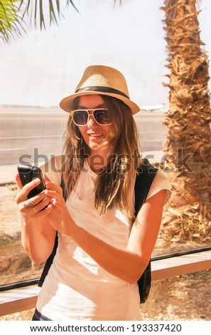 Traveler girl is near the airport window. Passenger woman using mobile phone in terminal. Air travel concept with happy female, who standing with hand luggage backpack (Sharm El Sheikh, Egypt).   - stock photo