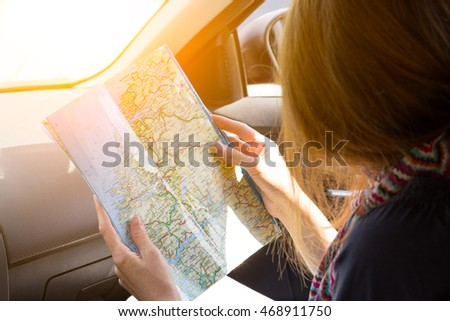 traveler girl sitting in the car looking map