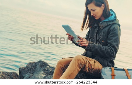 Traveler girl sitting on coast near the sea and working on digital tablet. Image with instagram filter - stock photo