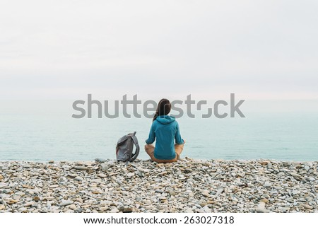 Traveler girl with backpack sitting in the lotus position on coast and enjoying view of sea, rear view - stock photo