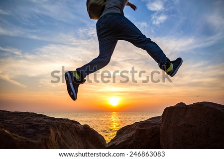 traveler jumping over rocks near the ocean at beautiful sunset