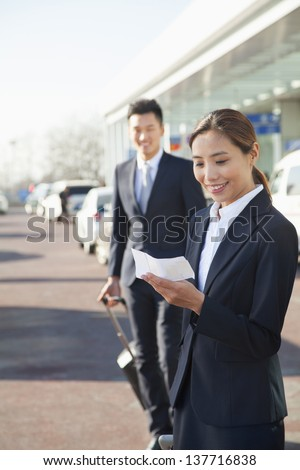 Traveler looking at ticket at airport arrivals area - stock photo