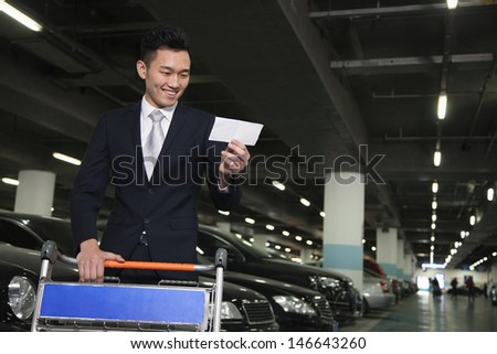 Traveler looking at ticket in airport parking lot - stock photo