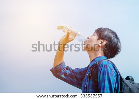 Traveler man looking bottle of water in the park