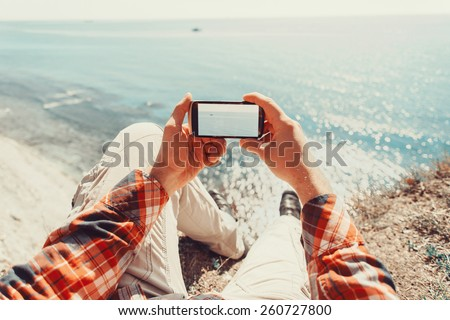 Traveler man taking photographs sea with smartphone. Point of view shot - stock photo