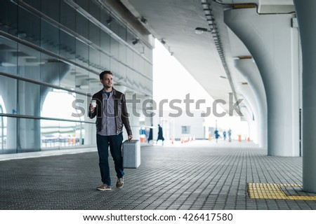 Traveler man walking with suitcase in the street near the airport terminal - stock photo