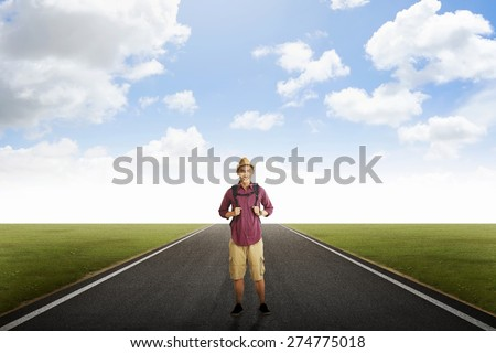 Traveler man with backpack posing on empty road - stock photo