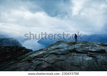 traveler on the top of the mountain with panoramic view - stock photo