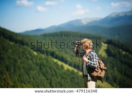 traveler on top of a mountain  looking through binoculars on landscape