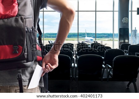 traveler presenting passenger tickets for flight at counter check-in airport