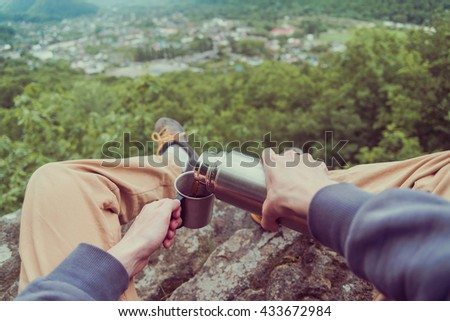 Traveler sitting on top of rock over the summer forest and pouring tea from thermos to cup. Point of view shot - stock photo