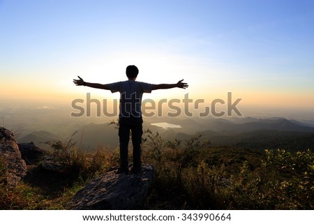 Traveler standing arms and watching the sunrise in Khao Luang Mt. at Ramkhamhaeng National Park Thailand