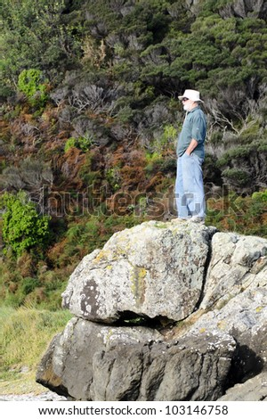 Traveler stands on a rock. - stock photo