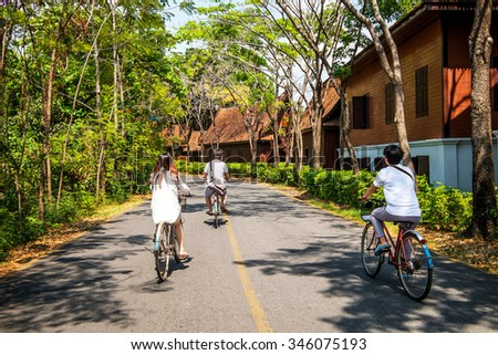 Traveler teenager ride a bicycles in parks under the umbrage