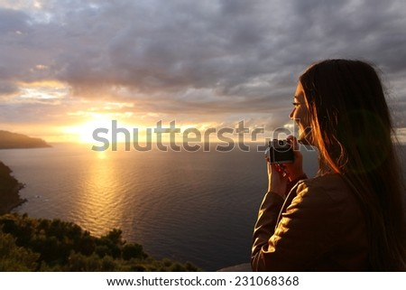 Traveler tourist girl taking photo of a sunset on the beach in vacations with a vintage slr camera - stock photo
