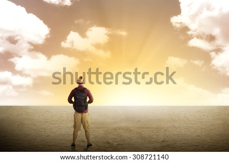 Traveler trekking in the desert with cloudy sky - stock photo