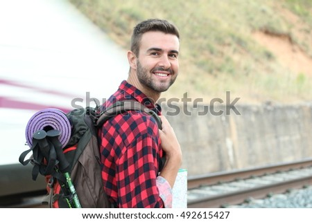 Traveler wearing backpack waiting railway at train station while a metro tube subway is passing by
